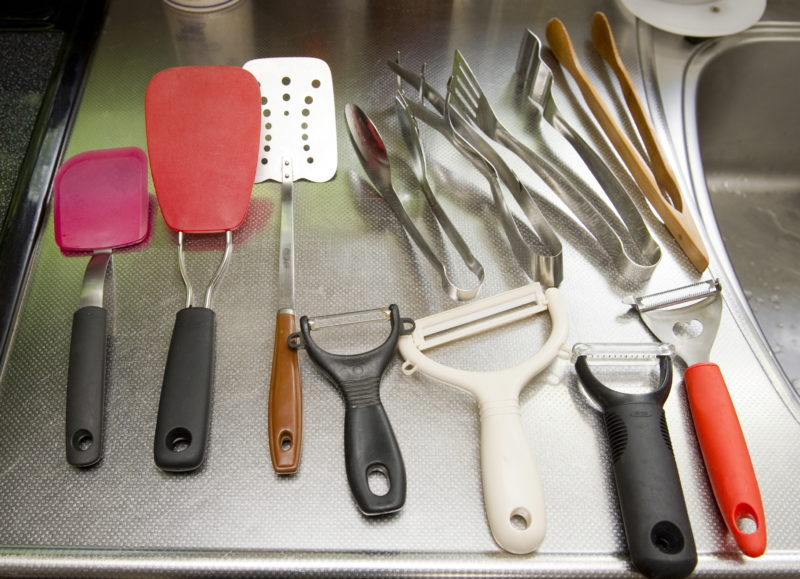 楽歩さんのキッチンで絶対必要なアイテムたちの画像。大小様々なヘラや、数種類の皮むき器、トングなどがずらり