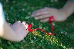 小指から伸びた赤い糸が繋がっている画像