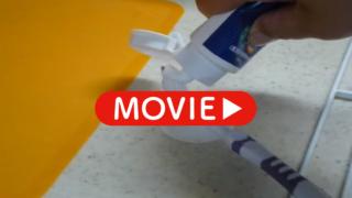 片手で歯磨き粉を歯ブラシにつけている画像のサムネイル