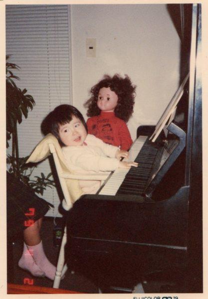 ピアノの前に座る幼女時代の楽歩さんの画像
