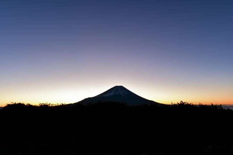 富士山の向こうから朝日が昇っている画像